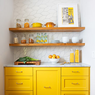 Mid-sized eclectic eat-in kitchen designs - Example of a mid-sized eclectic l-shaped medium tone wood floor and brown floor eat-in kitchen design in Austin with an undermount sink, recessed-panel cabinets, yellow cabinets, marble countertops, white backsplash, ceramic backsplash, white appliances, an island and white countertops