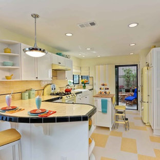 Inspiration for a traditional u-shaped separate kitchen in San Diego with a farmhouse sink, shaker cabinets, white cabinets, tile benchtops, yellow splashback, subway tile splashback, coloured appliances, multi-coloured floor and yellow benchtop.