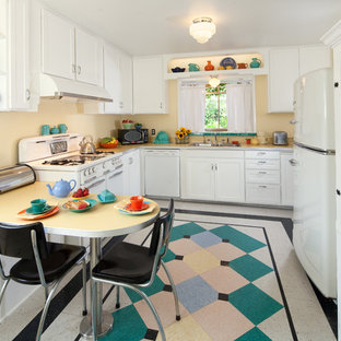 Mid-sized mid-century modern kitchen designs - Inspiration for a mid-sized 1960s u-shaped linoleum floor and multicolored floor kitchen remodel in Santa Barbara with a double-bowl sink, shaker cabinets, white cabinets, laminate countertops, white appliances, an island and white countertops