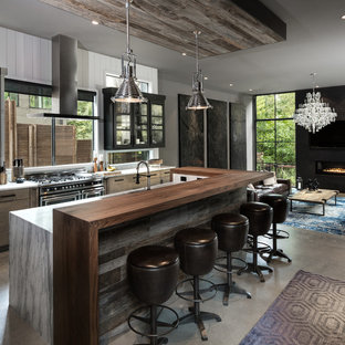 Cette photo montre une grande cuisine ouverte parallèle industrielle avec un placard à porte plane, des portes de placard en bois clair, un plan de travail en marbre, une crédence blanche, une crédence en bois, béton au sol, un îlot central, un électroménager noir et un sol gris.