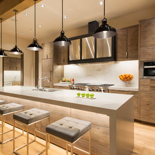 Inspiration for an expansive contemporary galley kitchen in Denver with flat-panel cabinets, beige cabinets, solid surface benchtops, white splashback, stone slab splashback, stainless steel appliances, light hardwood floors, with island, an undermount sink and brown floor.