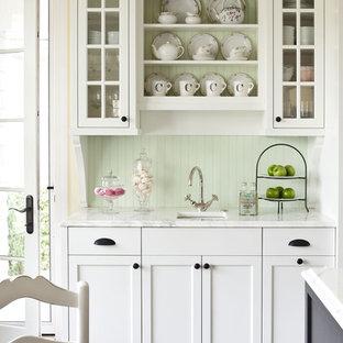 Foto di una cucina chic di medie dimensioni con lavello sottopiano, ante bianche, top in marmo, paraspruzzi verde e ante di vetro