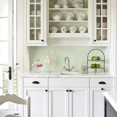 Example of a mid-sized classic kitchen design in Minneapolis with an undermount sink, white cabinets, marble countertops, green backsplash and glass-front cabinets