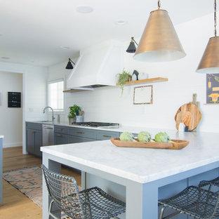 サンフランシスコの中サイズのエクレクティックスタイルのおしゃれなキッチン (ドロップインシンク、シェーカースタイル扉のキャビネット、グレーのキャビネット、大理石カウンター、白いキッチンパネル、シルバーの調理設備の、淡色無垢フローリング、グレーのキッチンカウンター) の写真