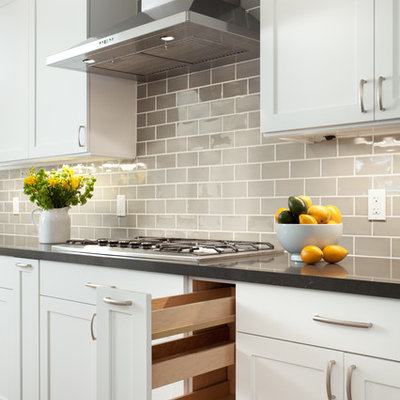 Example of a mid-sized minimalist l-shaped light wood floor and beige floor eat-in kitchen design in San Francisco with a drop-in sink, white cabinets, quartzite countertops, gray backsplash, ceramic backsplash, stainless steel appliances, an island and gray countertops