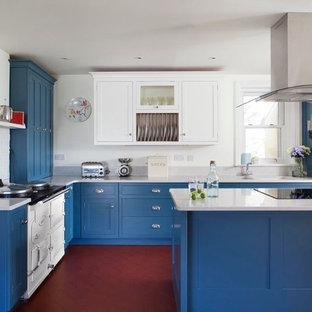 他の地域の中サイズのビーチスタイルのおしゃれなキッチン (シェーカースタイル扉のキャビネット、青いキャビネット、赤い床、白いキッチンカウンター) の写真