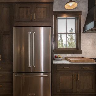 デンバーの大きいラスティックスタイルのおしゃれなキッチン (アンダーカウンターシンク、シェーカースタイル扉のキャビネット、濃色木目調キャビネット、クオーツストーンカウンター、ベージュキッチンパネル、サブウェイタイルのキッチンパネル、シルバーの調理設備の、淡色無垢フローリング、ベージュの床、白いキッチンカウンター) の写真