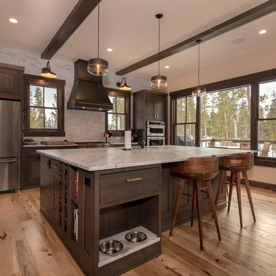 Example of a large mountain style l-shaped light wood floor and beige floor open concept kitchen design in Denver with an undermount sink, shaker cabinets, dark wood cabinets, quartz countertops, beige backsplash, subway tile backsplash, stainless steel appliances, an island and white countertops