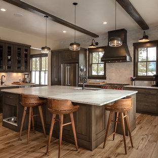 デンバーの大きいラスティックスタイルのおしゃれなキッチン (アンダーカウンターシンク、シェーカースタイル扉のキャビネット、濃色木目調キャビネット、シルバーの調理設備の、淡色無垢フローリング、白いキッチンカウンター、クオーツストーンカウンター、ベージュの床、ベージュキッチンパネル、サブウェイタイルのキッチンパネル) の写真
