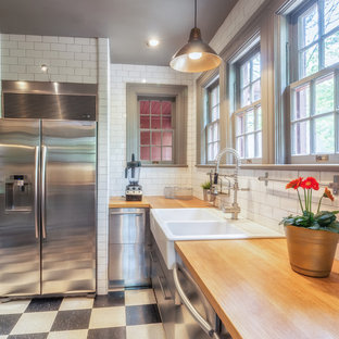 他の地域の小さいインダストリアルスタイルのおしゃれなキッチン (エプロンフロントシンク、フラットパネル扉のキャビネット、ステンレスキャビネット、木材カウンター、白いキッチンパネル、サブウェイタイルのキッチンパネル、シルバーの調理設備の、クッションフロア、黒い床) の写真