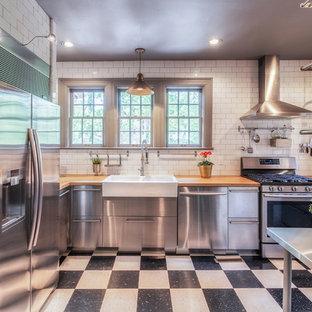 他の地域のインダストリアルスタイルのおしゃれなキッチン (エプロンフロントシンク、フラットパネル扉のキャビネット、ステンレスキャビネット、木材カウンター、白いキッチンパネル、サブウェイタイルのキッチンパネル、シルバーの調理設備、クッションフロア、黒い床) の写真