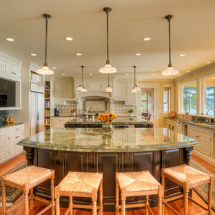 This is an example of a traditional u-shaped kitchen in Seattle with an undermount sink, raised-panel cabinets, white cabinets, panelled appliances, medium hardwood floors, multiple islands, brown floor and green benchtop.