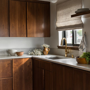 Photo of a midcentury l-shaped kitchen in Seattle with an undermount sink, flat-panel cabinets, medium wood cabinets, grey splashback, multi-coloured floor and grey benchtop.