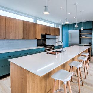 シアトルの大きいコンテンポラリースタイルのおしゃれなアイランドキッチン (アンダーカウンターシンク、フラットパネル扉のキャビネット、白いキッチンパネル、シルバーの調理設備の、淡色無垢フローリング、白いキッチンカウンター、ターコイズのキャビネット、サブウェイタイルのキッチンパネル、ベージュの床) の写真