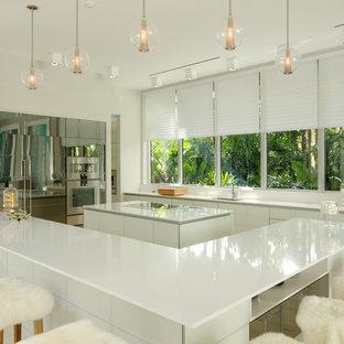 Offene, Große Moderne Küche in U-Form mit Unterbauwaschbecken, flächenbündigen Schrankfronten, weißen Schränken, zwei Kücheninseln, Quarzwerkstein-Arbeitsplatte, Elektrogeräten mit Frontblende und Keramikboden in Miami