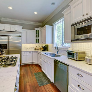 Small transitional galley eat-in kitchen in Raleigh with a double-bowl sink, recessed-panel cabinets, white cabinets, quartzite benchtops, white splashback, ceramic splashback, stainless steel appliances, medium hardwood floors and with island.
