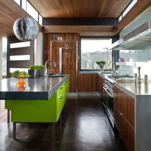 Inspiration for a contemporary kitchen remodel in San Francisco with concrete countertops, paneled appliances, flat-panel cabinets, glass sheet backsplash and dark wood cabinets