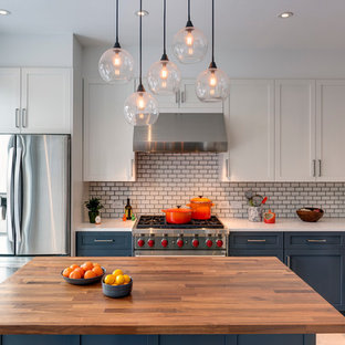 Transitional kitchen photos - Transitional l-shaped light wood floor kitchen photo in New York with shaker cabinets, gray cabinets, quartz countertops, white backsplash, stainless steel appliances, an island and subway tile backsplash