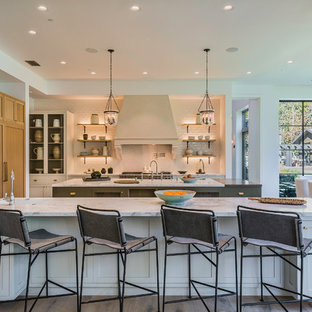 Large country single-wall eat-in kitchen in Los Angeles with marble benchtops, white splashback, subway tile splashback, light hardwood floors, multiple islands, beige floor, a farmhouse sink, recessed-panel cabinets, light wood cabinets and stainless steel appliances.