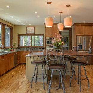 Ejemplo de cocina en U, rústica, con armarios estilo shaker, puertas de armario de madera oscura, salpicadero gris, electrodomésticos de acero inoxidable, suelo de madera en tonos medios, una isla, suelo marrón y encimeras verdes