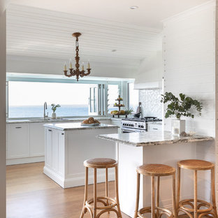 Inspiration for a mid-sized beach style u-shaped kitchen in Sunshine Coast with an undermount sink, shaker cabinets, white cabinets, granite benchtops, white splashback, ceramic splashback, stainless steel appliances, medium hardwood floors, with island, multi-coloured benchtop and brown floor.