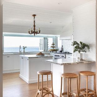 サンシャインコーストの中サイズのトロピカルスタイルのおしゃれなキッチン (アンダーカウンターシンク、シェーカースタイル扉のキャビネット、白いキャビネット、御影石カウンター、白いキッチンパネル、セラミックタイルのキッチンパネル、シルバーの調理設備、無垢フローリング、マルチカラーのキッチンカウンター、茶色い床) の写真