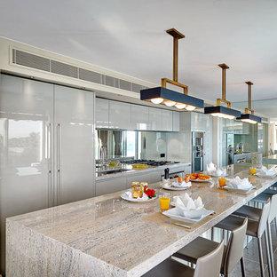 Inspiration pour une grande cuisine américaine linéaire design avec un évier encastré, des portes de placard grises, une crédence en carreau de miroir et un sol en carrelage de céramique.