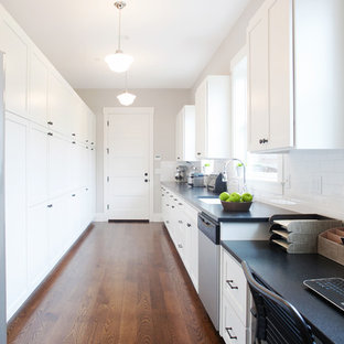 Transitional enclosed kitchen designs - Inspiration for a transitional single-wall enclosed kitchen remodel in Portland with an undermount sink, shaker cabinets, white cabinets, granite countertops, white backsplash, subway tile backsplash and stainless steel appliances