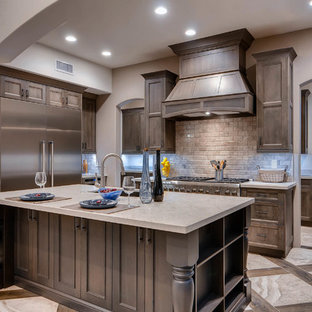 Mediterranean kitchen in Phoenix with an undermount sink, recessed-panel cabinets, quartzite benchtops, travertine splashback, stainless steel appliances, porcelain floors and multiple islands.