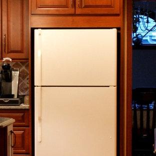 Geschlossene, Mittelgroße Klassische Küche in L-Form mit Unterbauwaschbecken, profilierten Schrankfronten, hellbraunen Holzschränken, Quarzwerkstein-Arbeitsplatte, Rückwand aus Keramikfliesen, weißen Elektrogeräten, hellem Holzboden und Kücheninsel in Chicago