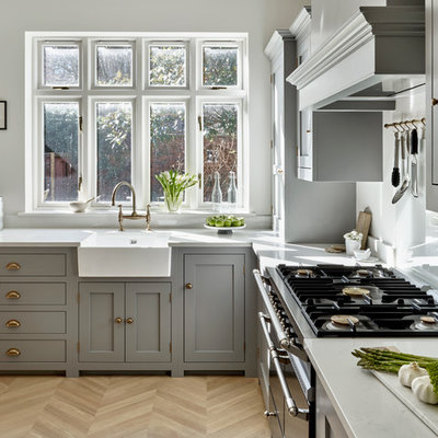 Example of a transitional l-shaped light wood floor eat-in kitchen design in London with a farmhouse sink, shaker cabinets, gray cabinets, an island and white countertops
