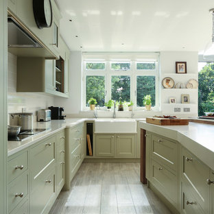 Photo of a large traditional u-shaped kitchen in London with a farmhouse sink, shaker cabinets, white splashback and with island.