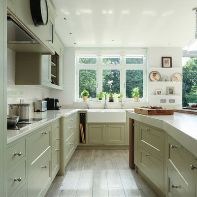 Example of a large classic u-shaped kitchen design in London with a farmhouse sink, shaker cabinets, white backsplash and an island