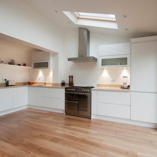 This is an example of a small contemporary l-shaped open plan kitchen in Surrey with a built-in sink, flat-panel cabinets, white cabinets, granite worktops, stainless steel appliances, light hardwood flooring, no island and beige worktops.
