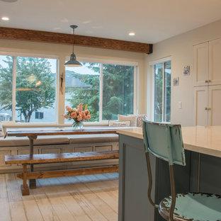 バンクーバーの大きいシャビーシック調のおしゃれなキッチン (アンダーカウンターシンク、シェーカースタイル扉のキャビネット、白いキャビネット、クオーツストーンカウンター、白いキッチンパネル、モザイクタイルのキッチンパネル、シルバーの調理設備、クッションフロア、白い床、白いキッチンカウンター) の写真