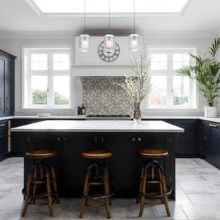 Design ideas for a large transitional u-shaped kitchen in Surrey with a farmhouse sink, blue cabinets, stainless steel appliances, an island, grey floor, white benchtop, shaker cabinets, beige splashback and mosaic tile splashback.