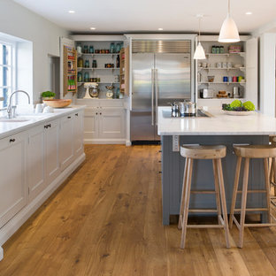 Medium sized classic l-shaped enclosed kitchen in Surrey with shaker cabinets, light hardwood flooring, an island and brown floors.