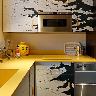 Photo of an eclectic l-shaped separate kitchen in London with flat-panel cabinets, stainless steel appliances, an integrated sink, yellow splashback, no island and yellow benchtop.