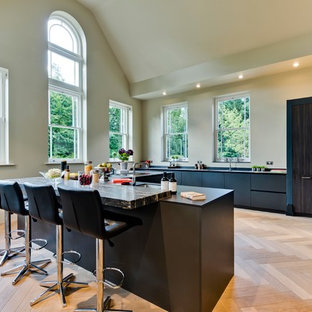 This is an example of a large contemporary u-shaped kitchen in Surrey with a submerged sink, flat-panel cabinets, black cabinets, light hardwood flooring, an island, beige floors, black worktops, beige splashback and integrated appliances.