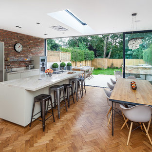 This is an example of a contemporary galley kitchen/diner in Surrey with marble worktops, red splashback, stainless steel appliances, medium hardwood flooring, an island and white cabinets.