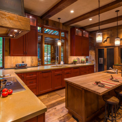 Large mountain style l-shaped eat-in kitchen photo in Other with an undermount sink, recessed-panel cabinets, red cabinets, wood backsplash, paneled appliances and an island