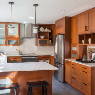This is an example of a small transitional u-shaped eat-in kitchen in San Diego with an undermount sink, shaker cabinets, brown cabinets, quartzite benchtops, white splashback, stone slab splashback, stainless steel appliances, porcelain floors, no island, grey floor and white benchtop.