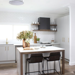 Inspiration for a mid-sized contemporary l-shaped kitchen in Sydney with flat-panel cabinets, grey cabinets, granite benchtops, white splashback, with island, white benchtop, subway tile splashback, panelled appliances, medium hardwood floors and beige floor.