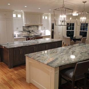 ボストンの大きいトランジショナルスタイルのおしゃれなキッチン (エプロンフロントシンク、インセット扉のキャビネット、白いキャビネット、御影石カウンター、マルチカラーのキッチンパネル、石スラブのキッチンパネル、シルバーの調理設備の、淡色無垢フローリング、黄色い床、マルチカラーのキッチンカウンター) の写真