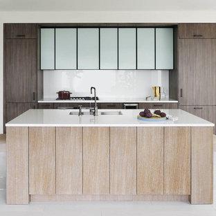 Ejemplo de cocina de galera, actual, con fregadero bajoencimera, armarios con paneles lisos, puertas de armario de madera en tonos medios, encimera de vidrio reciclado, salpicadero blanco, salpicadero de vidrio templado y una isla