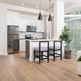 Diseño de cocina de galera, contemporánea, pequeña, con salpicadero blanco, salpicadero de azulejos tipo metro, electrodomésticos de acero inoxidable, suelo vinílico, una isla, suelo amarillo, encimeras blancas, armarios estilo shaker y puertas de armario blancas