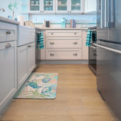Inspiration for a small coastal galley vinyl floor and yellow floor enclosed kitchen remodel in Wilmington with a farmhouse sink, shaker cabinets, white cabinets, stainless steel appliances and a peninsula