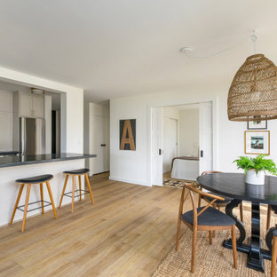 This is an example of a small modern u-shaped eat-in kitchen in Hawaii with a drop-in sink, shaker cabinets, white cabinets, soapstone benchtops, white splashback, subway tile splashback, stainless steel appliances, vinyl floors, with island, brown floor and black benchtop.