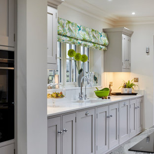 Photo of a large rural u-shaped open plan kitchen in Kent with recessed-panel cabinets, quartz worktops and multiple islands.