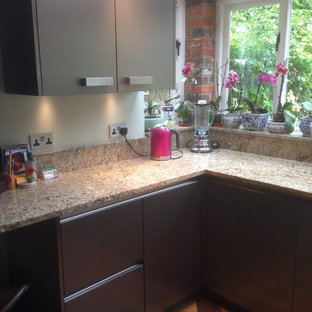 Small urban u-shaped kitchen in Buckinghamshire with a submerged sink, flat-panel cabinets, stainless steel cabinets, granite worktops, multi-coloured splashback, stone slab splashback, stainless steel appliances and ceramic flooring.